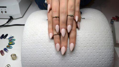 Dłonie z pierścionkami na poduszce, manicure matowy, różowy, salon piękności z malowaniem paznokci